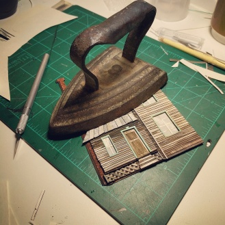 An 8lb. antique iron is used to ensure that all paper-cuts dry flat.